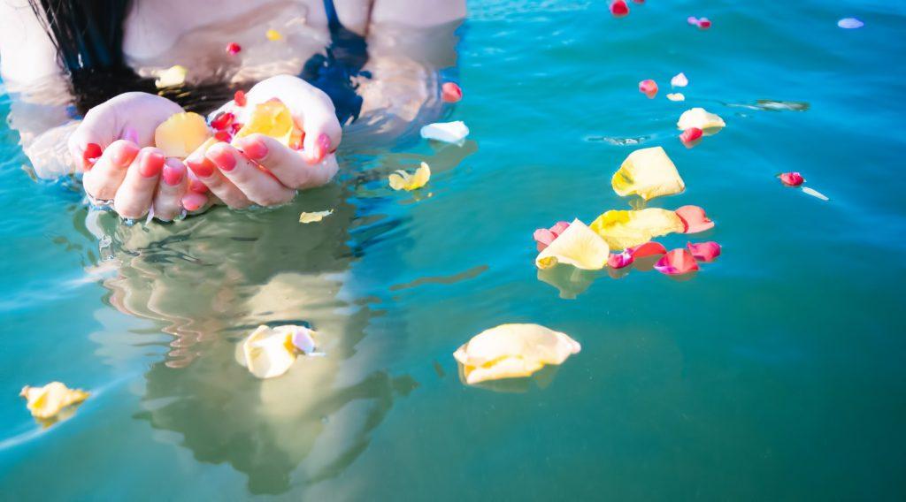 水着で花が浮かぶプールに入る女性